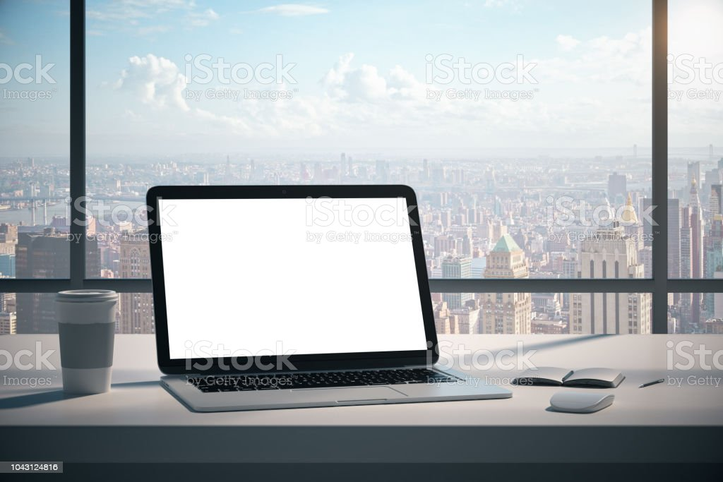 Modern designer office desktop with empty white laptop screen, coffee...