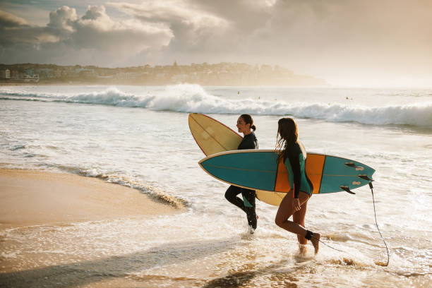 Modern determined girls go surfing stock photo