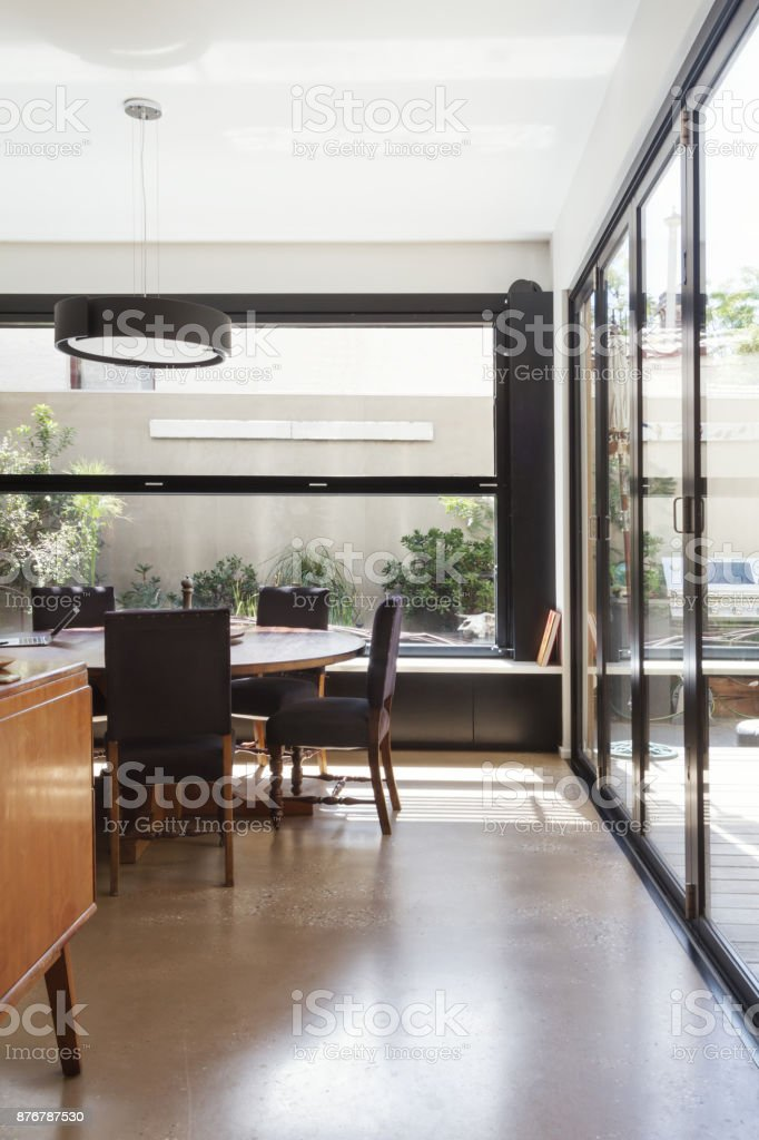 Modern dining room with polished concrete floor and glass bi fold doors stock photo