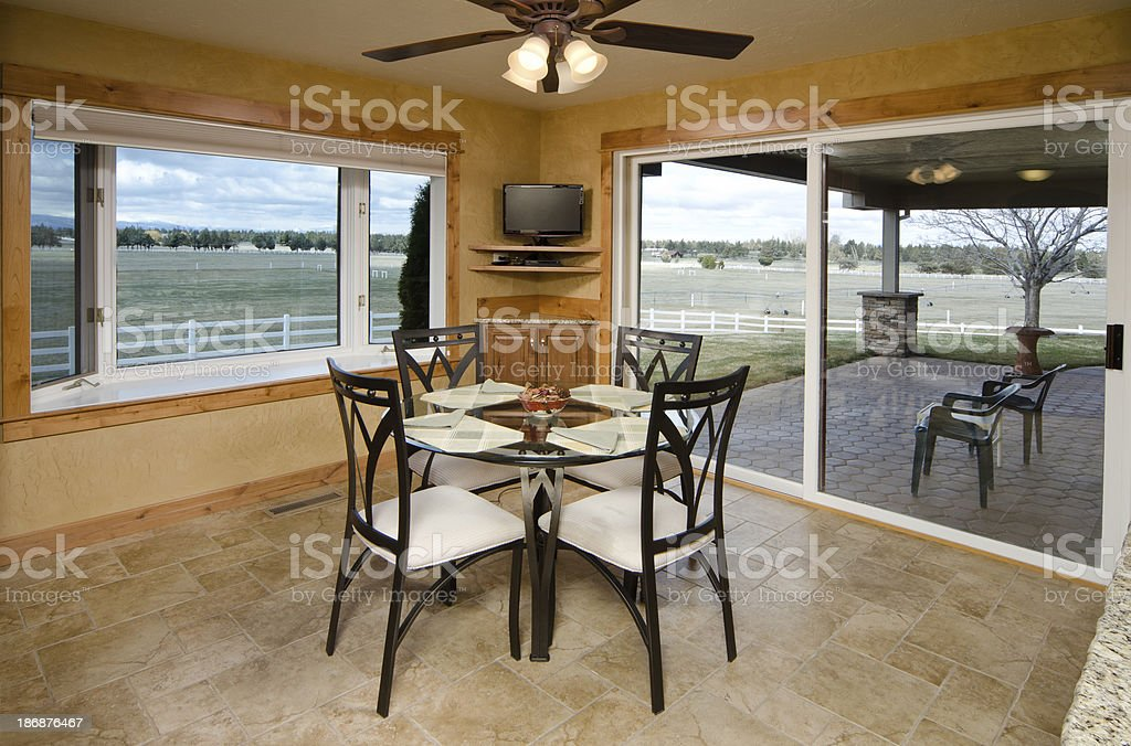 Modern dining room with tiled floors and a view of the deck.