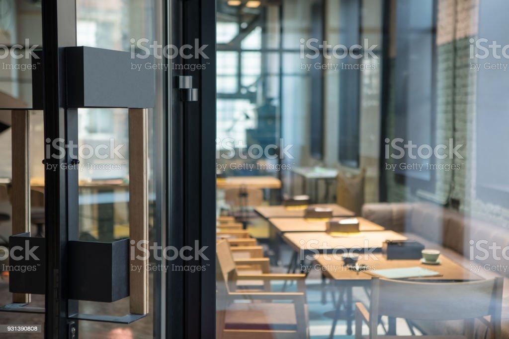 Moderne Türgriff auf der Holz-Glas-Tür vor dem Café. – Foto