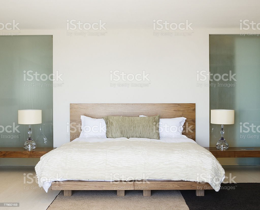 Modern double bed with bedside tables stock photo