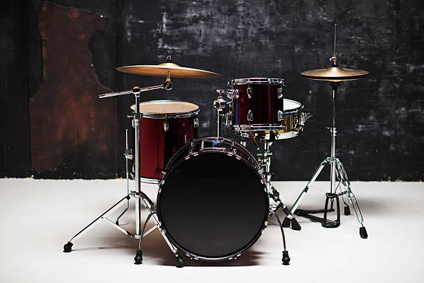 Modern drum set on black background in room Modern drum set on black background in room. Gold and red color drum kit stock pictures, royalty-free photos & images