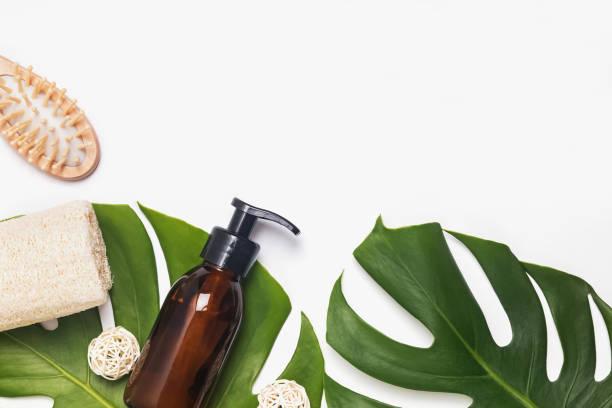 Modern eco bathroom essentials. Reusable dispenser, wooden hair brush and natural sponge stock photo