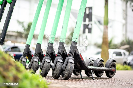 istock Modern eco electric city scooters for rent outdoors on the sidewalk. Alternative tourism, transportation around the city, bike replacement service. 1178359107