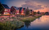 Long exposure night shot of Street with modern ecological middle class family houses with eco friendly river bank in Veenendaal city, Netherlands. Vintage look image