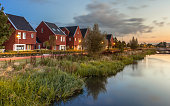 Long exposure night shot of Street with modern ecological middle class family houses with eco friendly river bank in Veenendaal city, Netherlands.