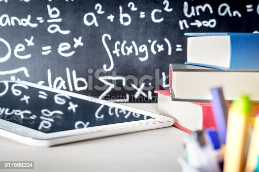 istock Modern education and e learning tools in school classroom table. Stack of books, tablet and pens with blackboard full or writing. 917599204