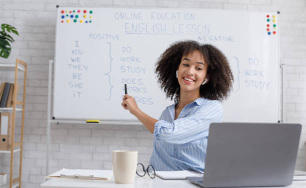 Modern education remotely. Cheerful african american woman points to blackboard and explains rules of english stock photo