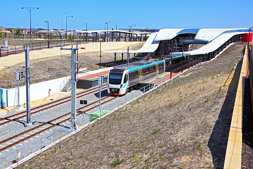 A modern electric commuter train departs a new station terminus sited close to an expanding suburban housing development.  Logos and ID numbers removed, train and building color changed, permission to photograph attached.