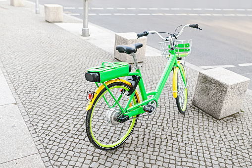 modern electric green bicycle parked at the sidewalk in the city