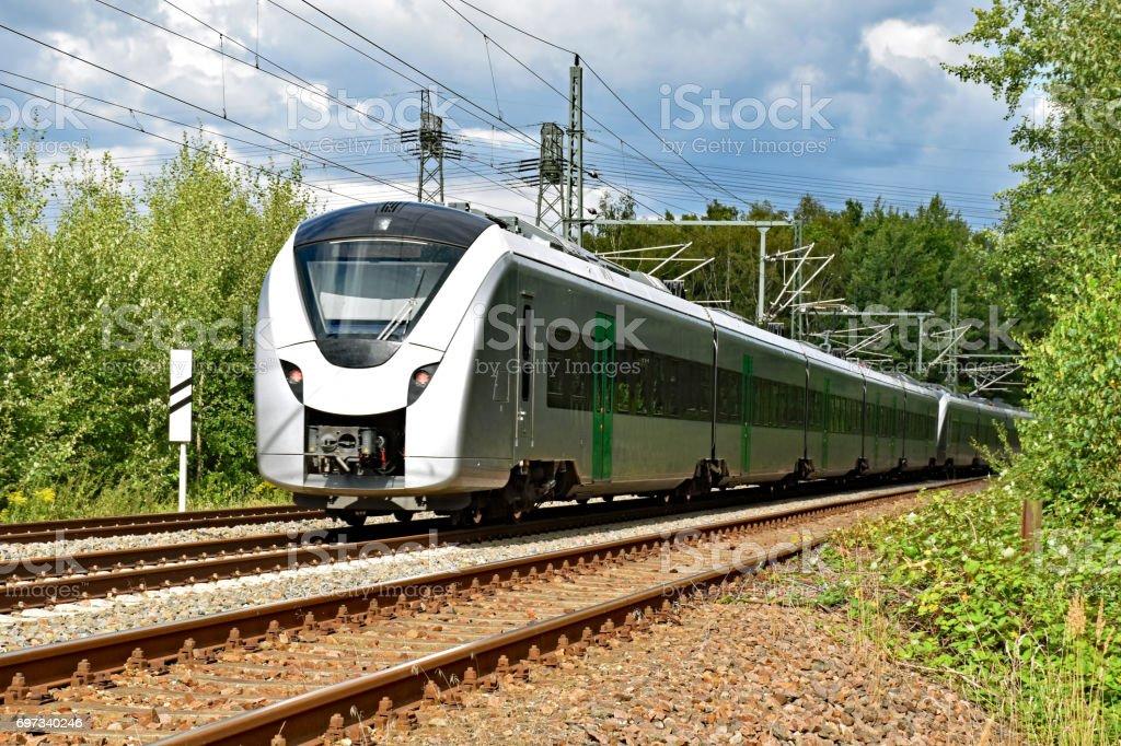 A modern electric regional train runs on a multi-lane track through natural surroundings stock photo