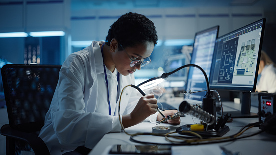 Modern Electronics Research, Development Facility: Black Female Engineer Does Computer Motherboard Soldering. Scientists Design PCB, Silicon Microchips, Semiconductors. Medium Close-up Shot