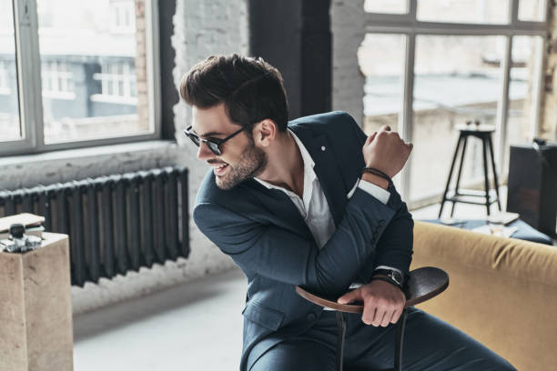 Modern elegance. Good looking young man in full suit looking away and smiling while sitting on the stool charming stock pictures, royalty-free photos & images