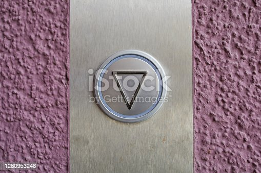 close up of an elevator button on a violet wall