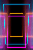 Modern empty abstract background illuminated by pink, blue, orange and green vertical rectangle neon lights / frames. Ceiling and background faded in the dark, left and right wall reflecting colors of the lights as in a hallway. A slight vintage effect added. 3D rendered image.