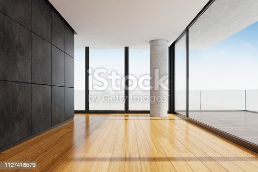 Modern and minimalist empty apartment with big panoramic windows and big terrace. Black stone marble wall tiles. Bamboo tiles on the floor. Big concrete column. Terrace with big wooded tiles and glass fence. Summer day scene. Copy space.