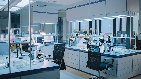 Modern Empty Biological Applied Science Laboratory with Technological Microscopes, Glass Test Tubes, Micropipettes and Desktop Computers and Displays. PC's are Running Sophisticated DNA Calculations.