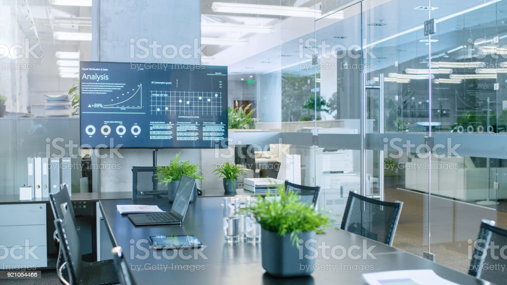 Modern Empty Meeting Room with Big Conference Table with Various Documents and Laptops on it, on the Wall Big TV Showing Company's Growth, Statistics and Pie Charts. stock photo