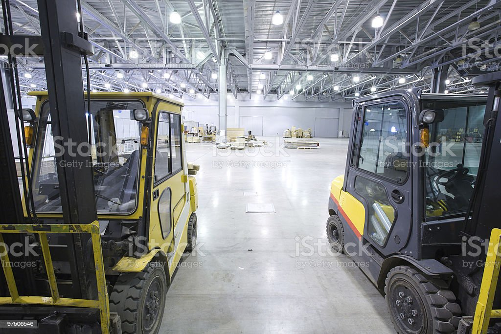 A modern, empty storehouse with two bobcats royalty-free stock photo