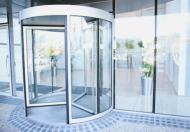 modern entrance with revolving door - entrance stock photos and pictures