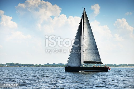 Modern expensive sport yacht sailing on a hot summer day, close-up. Dramatic cloudscape. England