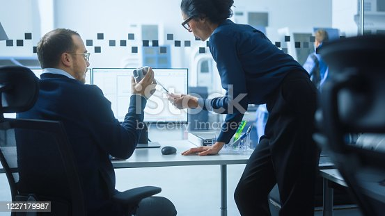 921019684 istock photo Modern Factory: Female Project Supervisor Talks to a Male Industrial Engineer who Works on Computer. They use CAD Software for Design, Development. High-Tech Industrial Facility. 1227179987