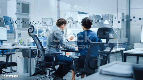 921019684 istock photo Modern Factory: Female Project Supervisor Talks to a Male Industrial Engineer who Works on Personal Computer. They use CAD Software for Design and Development of High-Tech Industrial Equipment 1227179997