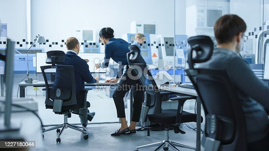 921019684 istock photo Modern Factory: Female Project Supervisor Talks to a Male Industrial Engineer who Works on Computer. They use CAD Software for Design, Development. In Background High-Tech Industrial Equipment 1227180044
