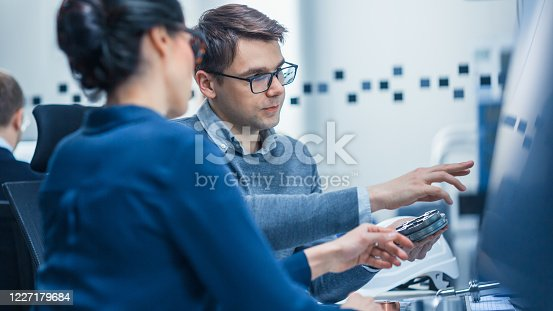 921019684 istock photo Modern Factory: Male Industrial Engineer Explains to Female Project Supervisor Functions of the Machine Part Comparing it to one on Computer Screen. They use CAD Software for Design, Development 1227179684
