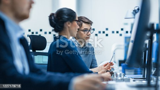921019684 istock photo Modern Factory: Male Industrial Engineer Explains to Female Project Supervisor Functions of the Machine Part Comparing it to one on Computer Screen. Modern High-Tech Industrial Factory Office. 1227179715