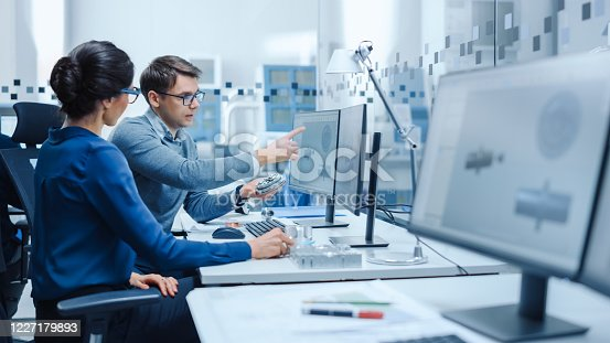 921019684 istock photo Modern Factory: Male Industrial Engineer Explains to Female Project Supervisor Functions of the Machine Part Comparing it to one on Computer Screen. They use CAD Software for Design, Development 1227179893