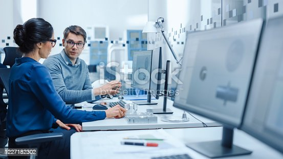 921019684 istock photo Modern Factory: Male Industrial Engineer Explains to Female Project Supervisor Functions of the Machine Part Comparing it to one on Computer Screen. They use CAD Software for Design, Development 1227182302