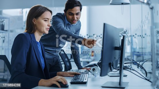 921019684 istock photo Modern Factory Office: Male Project Supervisor Talks to a Female Industrial Engineer who Works on Computer. Professional Teamwork, Young Specialists Solving Problems and Driving Technological Progress 1219894259