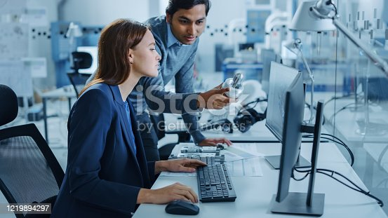 921019684 istock photo Modern Factory Office: Male Project Supervisor Talks to a Female Industrial Engineer who Works on Computer. Professional Teamwork, Young Specialists Solving Problems and Driving Technological Progress 1219894297