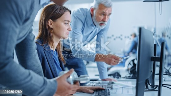921019684 istock photo Modern Factory Office: Project Manager and Supervisor Talk to a Female Engineer Works on Computer. Team of Professionals Solving Heavy Industry Problems, Having Discussion, Pointing at Display 1219894289