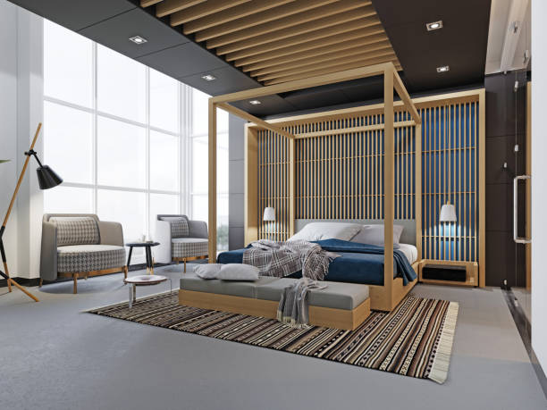 Modern fashionable design of a bedroom, a bed with a canopy. TV unit, two soft chairs, a wooden bed with four-poster.