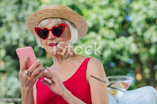 Calling grandchildren. Modern fashionable grandmother calling her grandchildren using pink smart phone