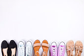 International womens day sale clearance. Variety row of different colorful casual shoes, sandals, white background. Spring-summer collection. White, purple, red low top sneakers. Copy space, top view.