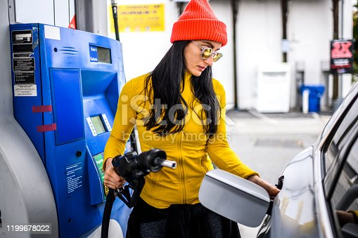 A contemporary woman holding the gas pump nozzle at a fuel station.