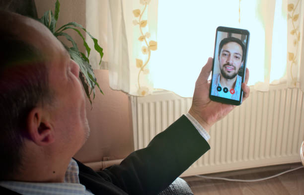 Modern father and son video chatting with phone, with plant on background stock photo