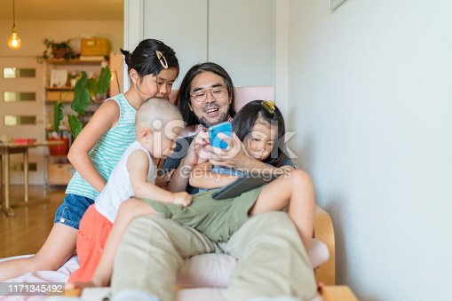 A modern father is taking care of his children at home.