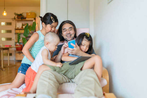 modern father taking care of his children at home - immagine foto e immagini stock