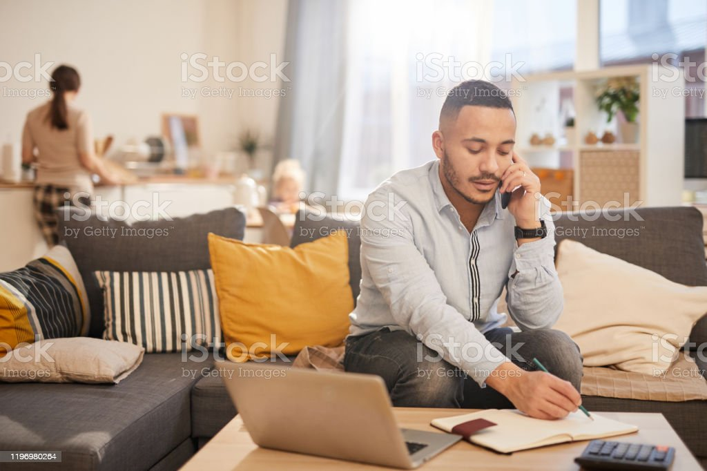 Modern Father Working from Home Portrait of modern mixed race man speaking by phone while working from home in cozy interior, copy space Adult Stock Photo