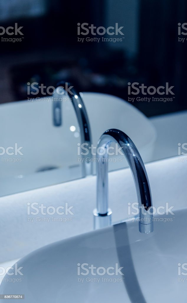 Modern faucet reflected in bathroom mirror stock photo