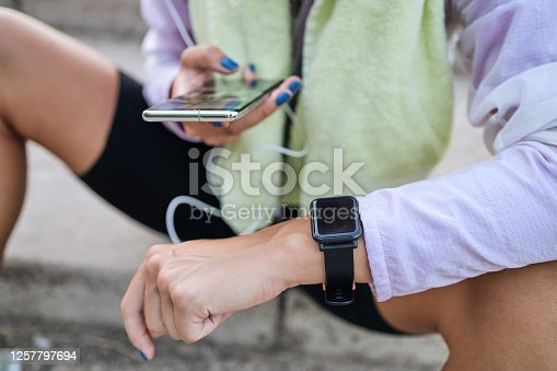 Young female athlete checking her pulse at the smart watch after she finished run with a female friend