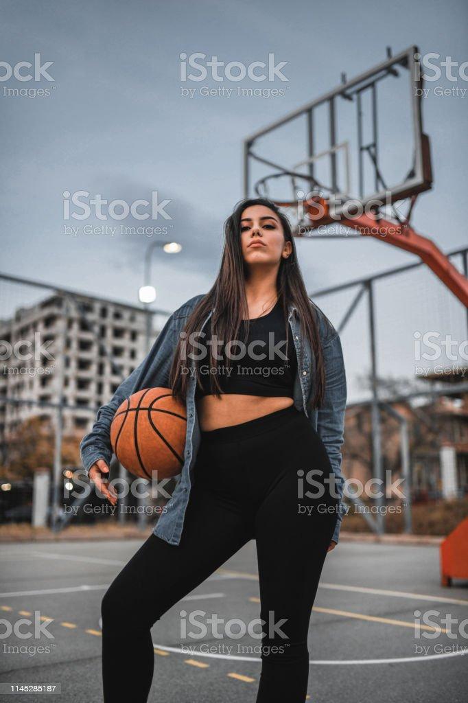 Modern Female Posing On Basketball Field