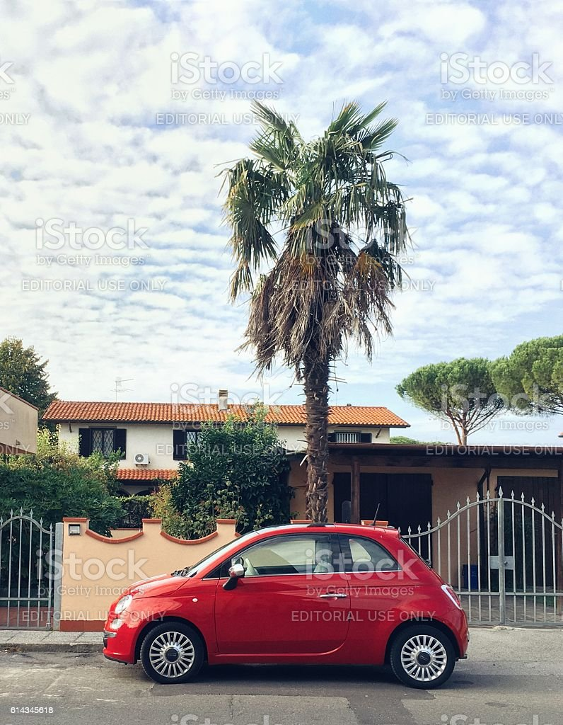 Modern Fiat CInqecento parked near palm trees and pines - foto stock