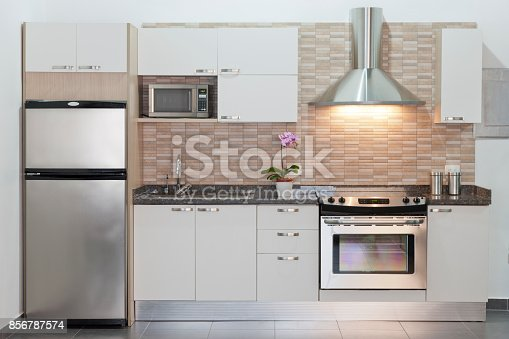 Small or compact modern kitchen with appliances. Contemporary style. Sparse design. White cabinets. Example of design for small architectural spaces. Front view, horizontal composition. Kitchen background.