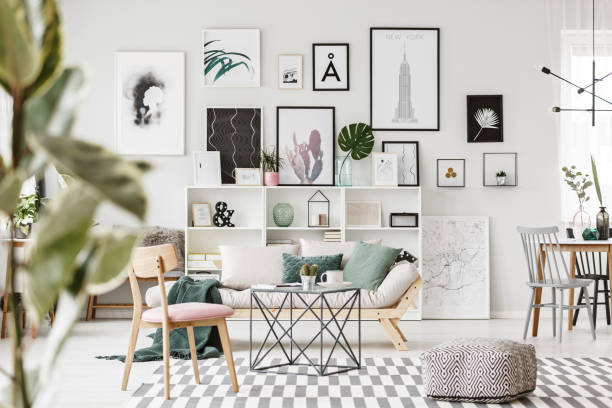 Modern flat interior with posters Patterned pouf, wooden chair and table on carpet in modern flat interior with settee against the wall with posters home decor stock pictures, royalty-free photos & images